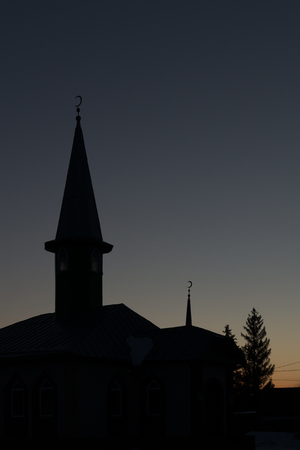 minuet: Muslim Mosque in silhouette with the crescent clearly visible on the minuet. Stock Photo