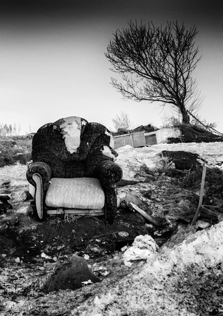 detritus: Single abandoned armchair in a deteriorating state surrounded by detritus as a tree leans over in the background. Monochrome black and white image. Stock Photo
