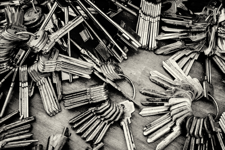 metal monochrome: Piles of blank metal house keys awaiting to be cut rest in a heap. Monochrome toned image. Stock Photo