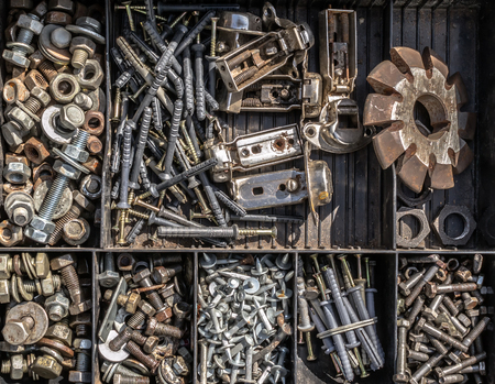 segregated: A toned image in color of an assorted collection of used nuts and bolts in a segregated tray for sale at a local market stall in Russia, Sterlitamak.