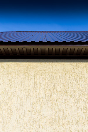 vibrant colours: Domestic house photograph of a building roof with vibrant colours and a clear blue sky. Copy space area on the wall. Vertical composition with nobody.