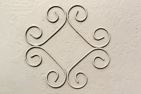 industrially: Single pattern of wrought iron forming a symmetrical pattern on a industrially grey paint background