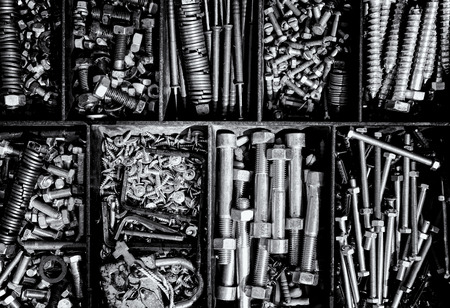 chaos order: Piles of nuts, bolts, and washers create an industrial themed background. Square containers create a uniform or order amongst the chaos of the metallic supplies. Monochrome black and white image.