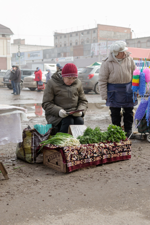 waits: STERLITAMAK - RUSSIA 9TH APRIL 2016 - Russian market trader reads a book as she waits for customers to buy her dill and parsley herbs and spring onions at a stall in Sterlitamak, Russia in April 2016. Editorial