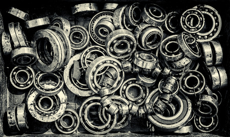 chromium plated: Assorted pile of ball bearing wheels in different sizes creates a retro themed industrial background. Toned Image in Black and White Monochrome.