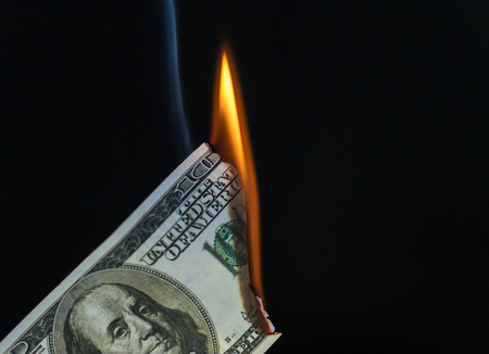 Smoke and fire rises from a burning 100 dollar USA American dollar note. Black background with copy space area for finance related wealth designs and ideas.