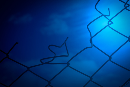 nightime: Broken wire chain link fence with blue sky and clouds in the background. Dusk nightime image with vibrant midnight blue tones.