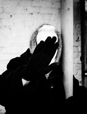 obscuring: An old woman in black uses her hand to hide her face from the camera. The gesture indicates her desire for protection and anonymity. Stock Photo