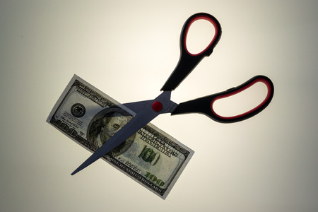 devaluation: Stainless steel scissors prepares to cut through an American USA 100 dollar bill. White uplit background and copy space area for finance budget cuts concepts.