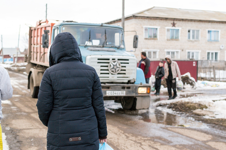 17th of march: REIFKA - RUSSIA 17TH MARCH 2016 - Residents prepare to throw their domestic rubbish into a collection lorry, as part of their domestic routine in Reifka, Russia in March 2016 Editorial