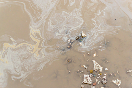 grimy: Weak Oil spill on the surface of a muddy grimy puddle of water. Stock Photo