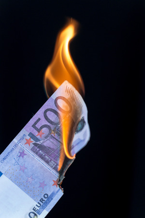 euro area: Single 500 EURO bankote on fire set against a black background with copy space area for finance waste themed ideas and concepts. Stock Photo