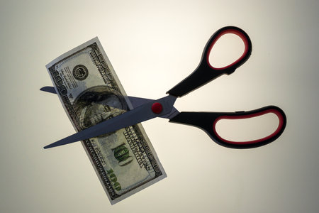 cut through: Stainless steel scissors prepares to cut through an American USA 100 dollar bill. White uplit background and copy space area for finance budget cuts concepts.