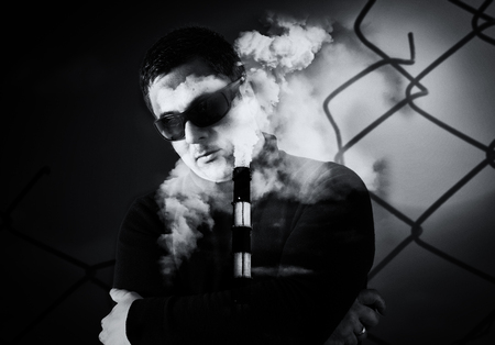 unknown men: Double exposure creative image of a man wearing sunglasses with a large industrial chimney stack and wire fence background.