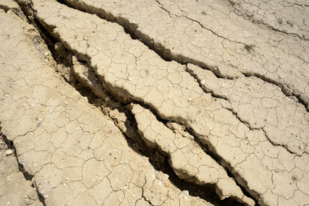 fissures: Fissures and large cracks in a dried mud background. Backdrop for environmental drought ideas and designs.