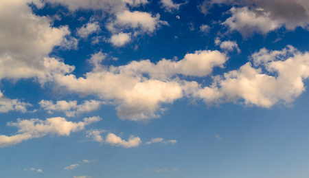 blue  backgrounds: White fluffy clouds and a blue sky background used for composite backgrounds and designs.