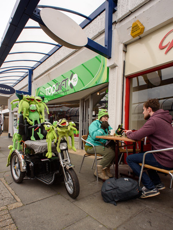 obsessed: WITHAM - ENGLAND 25TH APRIL 2016 - A women sits at a cafe with a young man next to her frog covered mobility scooter in Grosvenor Square in Witham in april 2016