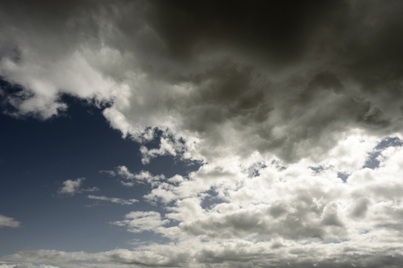 cloud formations: Grey clouds with white areas set against a dark blue spring sky. Sunlight shines through the patches of wispy cloud formations.