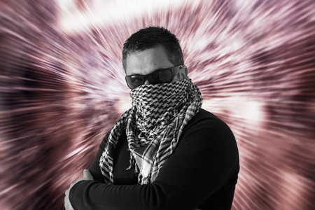 keffiyeh: Mysterious single man wearing sunglasses and a keffiyeh with crossed arms with a defocused zooming red coloured background. Stock Photo