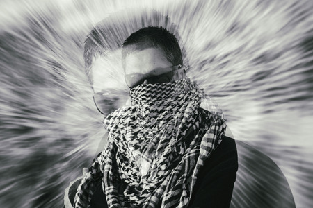 zooming: Mysterious single man wearing sunglasses and a keffiyeh with crossed arms with a defocused zooming coloured background using a double exposure effect.