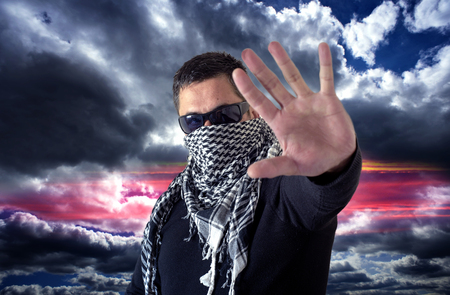 keffiyeh: Single man wearing black sunglasses and a keffiyeh uses his hand to give the signal to stop sign. Colored cloud background.