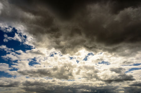 cloud formations: Grey clouds with white areas set against a dark blue spring sky. Sunlight shines through the patches of wispy cloud formations .