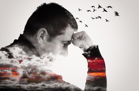 Doble efecto de la exposición de un hombre que piensa con el puño en alto a la frente. Las nubes cubren el pecho y los brazos como los pájaros vuelan de su cabeza.
