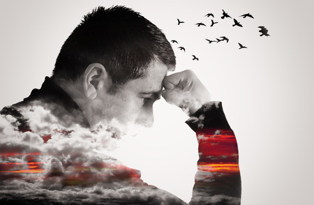 Double exposure effect of a man thinking with fist raised to forehead. Clouds cover his chest and arms as birds fly from his head.