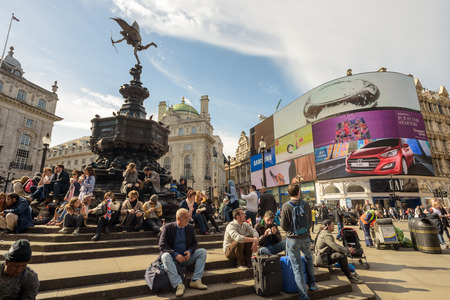 eros: LONDON - ENGLAND 1ST MAY 2016 - People sit and rest in the hot sun by the Eros Statue in Londons Piccadilly Circus during the May Day Bank Holiday in 2016 on May the 1st
