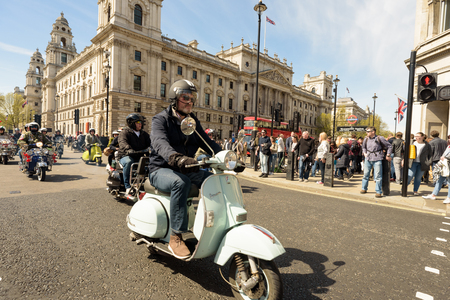 LONDON - ENGLAND 1ST MAY 2016 - Mods on their Vespa and Lambretta Scooters ride through Parliament Square as they travel on the London to Brighton Rally on May the 1st 2016