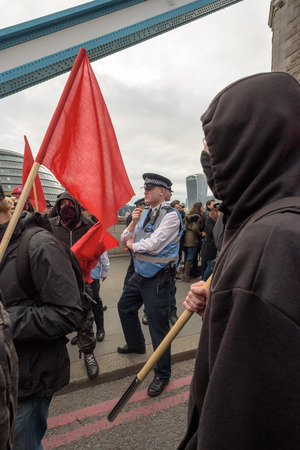 anarchist: LONDON - ENGLAND 1ST MAY 2016 - A PCSO Police Community Support Officer stands amongst a masked Anarchist group on Tower Bridge London during the May Day Bank Holiday rally on the 1st of May 2016.