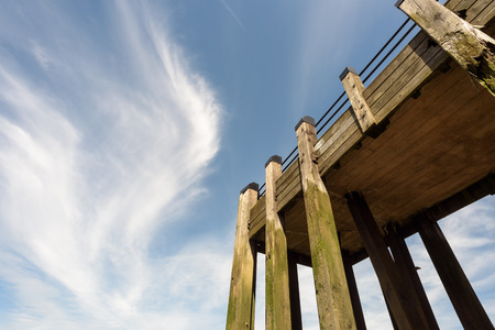 wispy: Wooden pier with tall beams and set against a blue sky with wispy white clouds