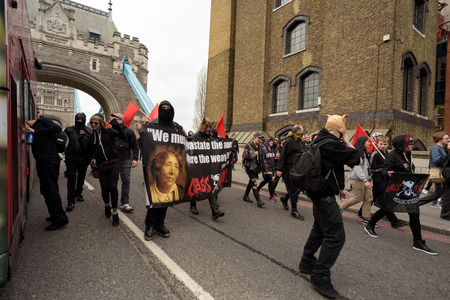 hidden danger: LONDON - ENGLAND 1ST MAY 2016 - An anarchist group with a slogan and masks move across Tower Bridge in London during the May Day Bank Holiday rally on the 1st of May 2016.