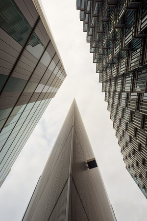 architectural designs: Tall modern business buildings in London City with a white sky and reflections. Architectural designs with copy space.