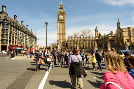 parliament square: LONDON - ENGLAND 1ST MAY 2016 - Tourists use a pedestrian crossing on Parliament Square in London outside Big Ben during the May 1st Bank Holiday in England