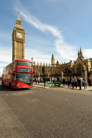 parliament square: LONDON - ENGLAND 1ST MAY 2016 - Modern red bus travels past Big Ben, Parliament Square in London during the May the 1st Bank Holiday in England