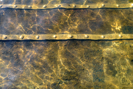 water stained: Stained metal underwater with a water wave pattern from natural movement and sunlight Stock Photo