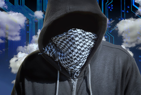 mainframe: Hooded and masked computer hacker thief with a cloud computer based background. Unknown technology threat to the cloud mainframe idea. Copy space area.