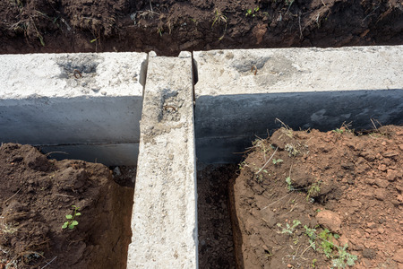 trenching: Grey construction concrete building blocks used for the foundations of a self-built house. Trenching and dug out earth surround the structure