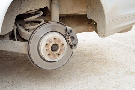 brake disc: Car brake disc on a jacked up car with no tyre. Copy space area for mechanical auto-service designs.