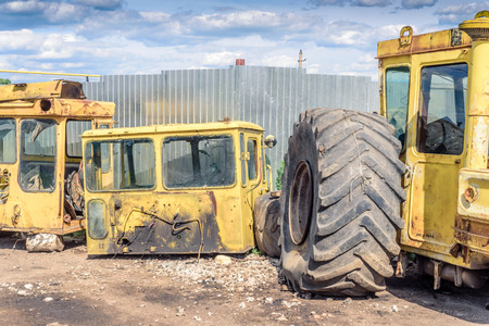 breakers: Broken and salvaged large yellow industrial machine cabins at a scrap breakers yard in non-working condition. The cabin compartments have been stripped of working parts.