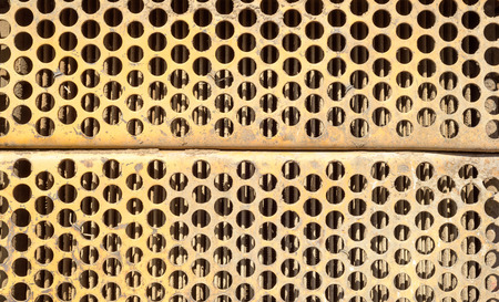 airflow: Orange rusted ventilation grill with many circular holes used as airflow for radiators on industrial machines and vehicles.