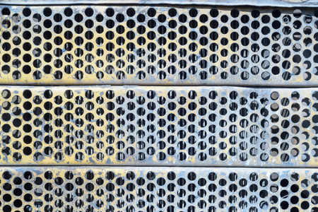 airflow: Blue stained and rusted rusted ventilation grill with many circular holes used as airflow for radiators on industrial machines and vehicles.