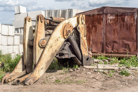 front loader: Broken and salvaged large yellow industrial machine mechanical grab frontloader at a scrap breakers yard in non-working condition. The lifting section has been stripped of working parts. Stock Photo