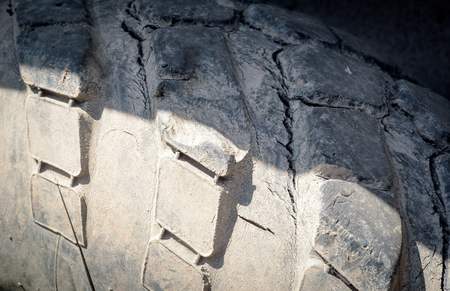 peeling rubber: Cracked and damaged worn industrial vehicle tyre with copy space area for mechanical service concepts