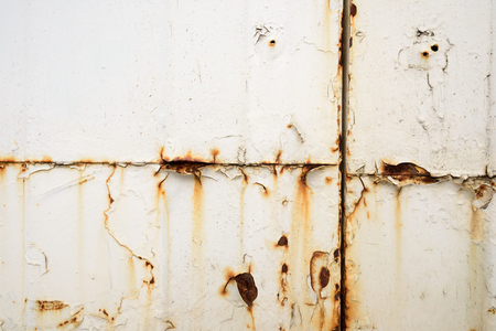 Grunge look of orange rusting metal on a painted white surface with bleeding into the paintwork