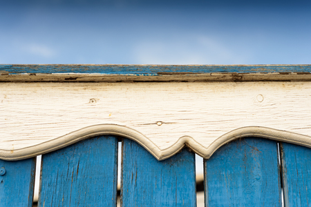 Intricate and ornate carved wooden detail rail on a blue painted fence with blue sky and copy space area.