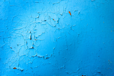 daubs: Bright vibrant and striking blue paint with visible cracking and flaking due to rust on a metal surface. Copy space area with shadows from natural sunlight.