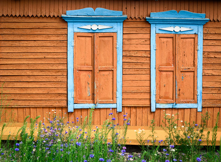 Two ornate hard carved wooden window frames in blue paint with closed orange hatches on a wood house exterior wall with wild flowers growing.