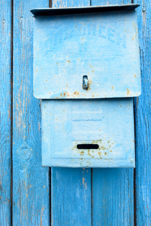metal post: Blue retro style metal post box on a wooden blue domestic fence